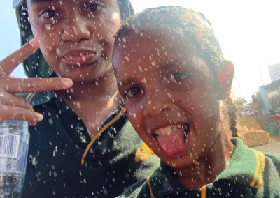 boy and girl posing for the camera while raining