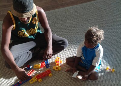 man and toddler playing on the ground with toys