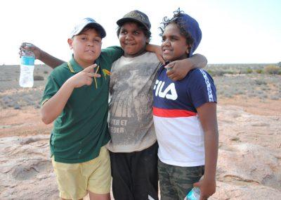 three boys posing for the camera with their arms around them