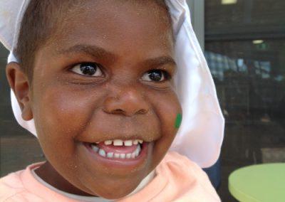 toddler wearing white hat smiling at the camera